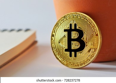 Golden Bitcoin and notebook on white background