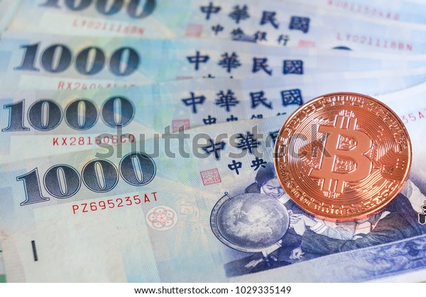 Golden bitcoin on 1000 Taiwanease dollar bills background, with copy space.