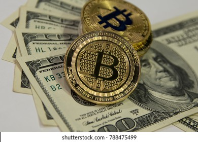 golden bitcoin on background of one hundred dollar bills