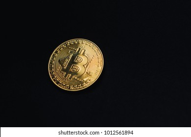 Golden bitcoin on black background with copy space. Cryptocurrency mining concept