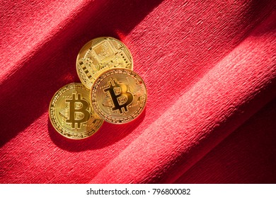 Golden bitcoin on burgundy or red background, cryptocurrency