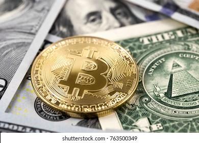 golden bitcoin on dollars close up