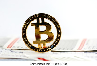A golden bitcoin on graph and diagrams on white  background.