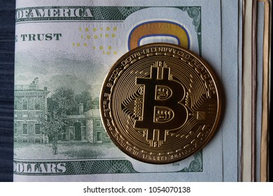 Golden bitcoin on a hundred-dollar bill.