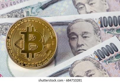 Golden Bitcoin on Japanese Yen banknote background.