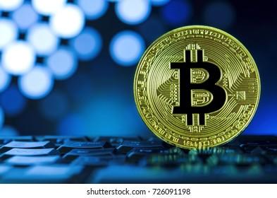 Golden bitcoin on keyboard against digital blue background. Virtual money