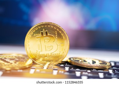 Golden bitcoin on keyboard with defocused blue backgroud.  (new virtual money)