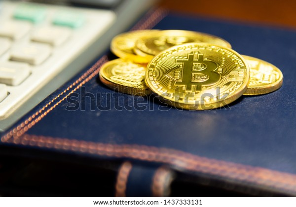 Golden bitcoin on leather book cover. Virtual cryptocurrency concept.