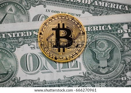 golden bitcoin on money bills background