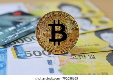 Golden Bitcoin on South Korea Won Banknotes background with credit cards