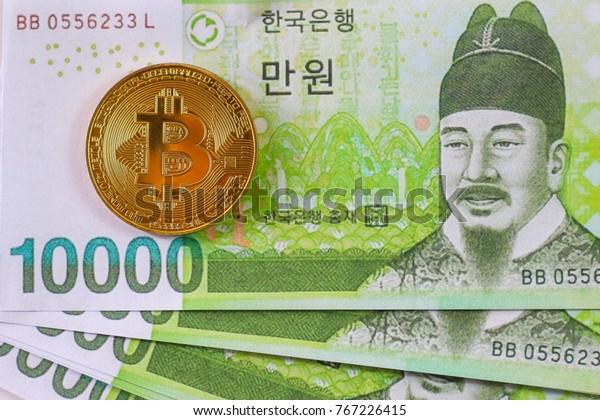 Golden Bitcoin on South Korea Won Banknote background