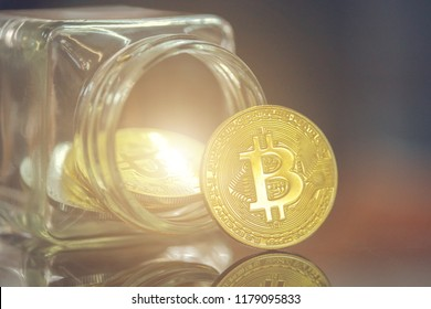 Golden Bitcoin on the table In a glass .Bitcoins and New Virtual money concept.Golden coin with icon letter B.Mining or block chain technology.