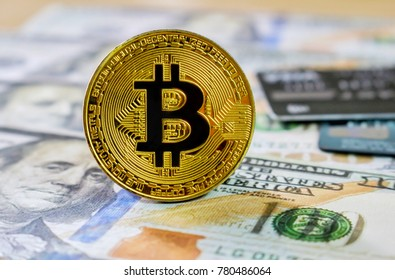 Golden Bitcoin on Us Dollar Banknotes background with credit card