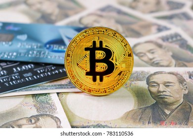 Golden Bitcoin On Yen Japan banknotes background with credit cards