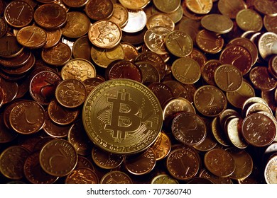 Golden bitcoin over a stack on penny coins