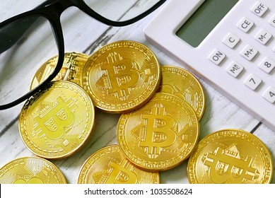 Golden bitcoin replica with eyewear and calculator. Business and finance concept.