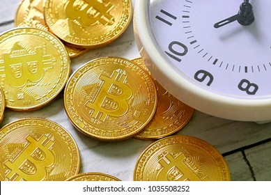 Golden bitcoin replica and table clock on white wooden background. Business and finance concept.