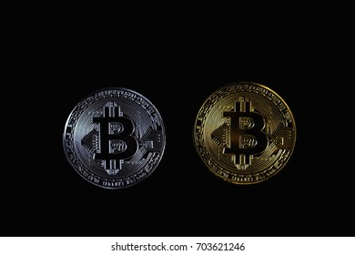 Golden bitcoin and Silver bitcoin isolated on black background