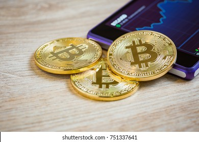 Golden bitcoin and smartohone on wooden background. Cryptocurrency concept