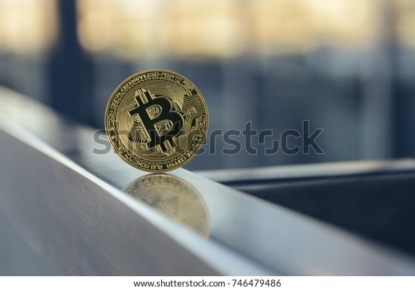 golden bitcoin standing on metal handrail