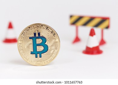 Golden bitcoin and two red cones on white background