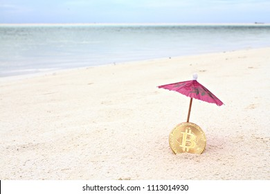 Golden Bitcoin under the paper umbrella on the beach, shallow focus