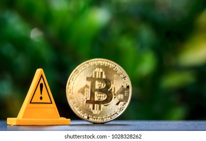 Golden bitcoin and warning sign on a nature background.Concept Bitcoin is a risky investment.