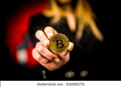 golden bitcoin in a woman's hands