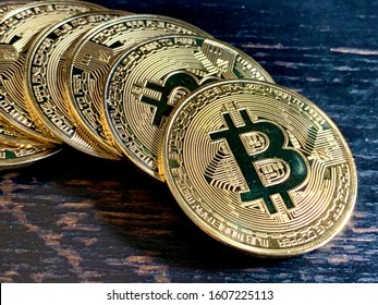 Golden bitcoins closeup on faded black wooden table