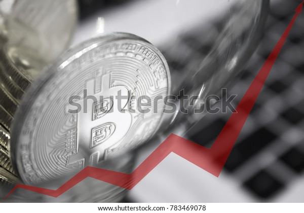 golden bitcoins in a cocktail glass, red arrow of the graph is directed upwards