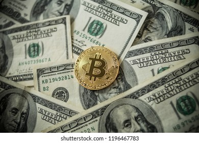Golden Bitcoins Coins lying on dollars.