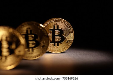Golden Bitcoins Coins on black background. Bitcoin cryptocurrency. Business concept.