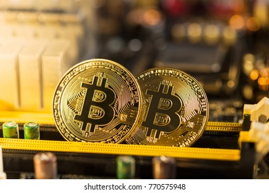 Golden bitcoins. Cryptocurrency on computer motherboard.