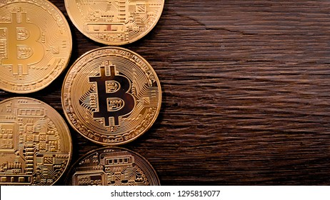 Golden bitcoins on a dark wooden background. Bitcoin is a convenient payment in a global economy market. Virtual digital currency and financial investment trade concept. Blockchain transfers concept.