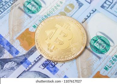 Golden bitcoins on dollar bills, closeup