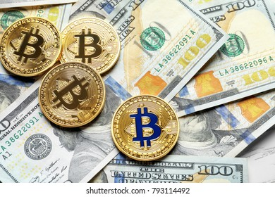 Golden bitcoins on dollar bills