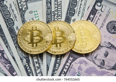 Golden bitcoins on a dollars banknotes