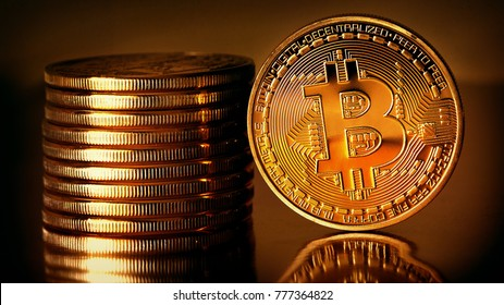 Golden Bitcoins on a gold background .Photo (new virtual money ) New crypto currency in the form of the coins.