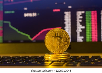 Golden bitcoins on keyboard with traiding chart background