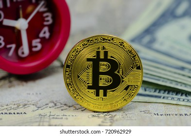 Golden Bitcoins on red clock,banknotes background.Photo of golden bitcoin (new virtual currency)