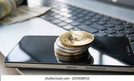 Golden bitcoins on a top of other coins and on the smart phone and on a laptop. Bitcoin crypto currebcy. Digital currency. Profit from mining crypto currencies. Miner with dollars from trading.