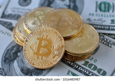 Golden bitcoins on US dollars