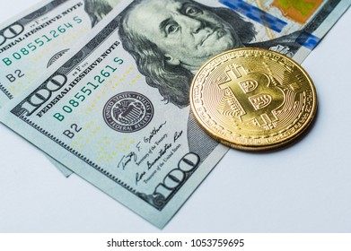 Golden Bitcoins on US dollars. Digital currency close-up. New virtual money. Crypto currency top view. Real coins of bitcoin on banknotes of one hundred dollars.