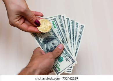 Golden bitcoins on us dollars in the hands electronic money exchange concept