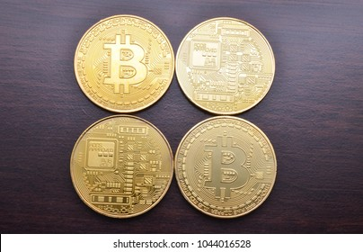 Golden Bitcoins on wooden desk background. Selective focus.