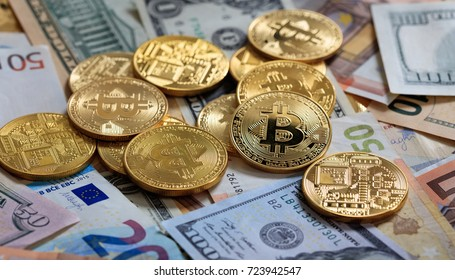 Golden bitcoins stacked on dollar and euro banknotes background