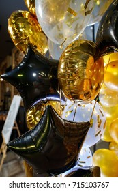 golden and black balloons. The photo zone is decorated with black and yellow balloon. stylish party with balloons. balloon in the form of a star. round golden balloon.