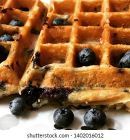 Golden blueberry waffles on a white surface with fresh blueberries in the foreground.