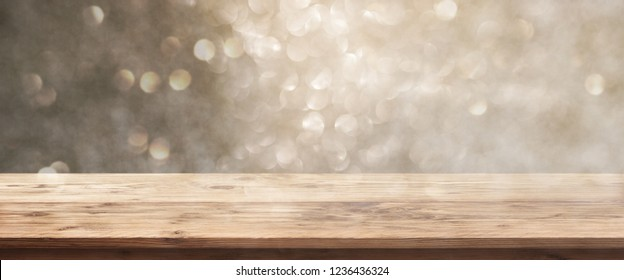 Golden bokeh background with rustic wooden table for a christmas decoration