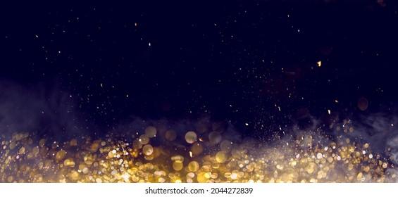 Golden bokeh glister on dark background